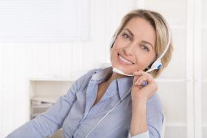 Frau mit Headset in blauer Bluse im Büro im Verkauf